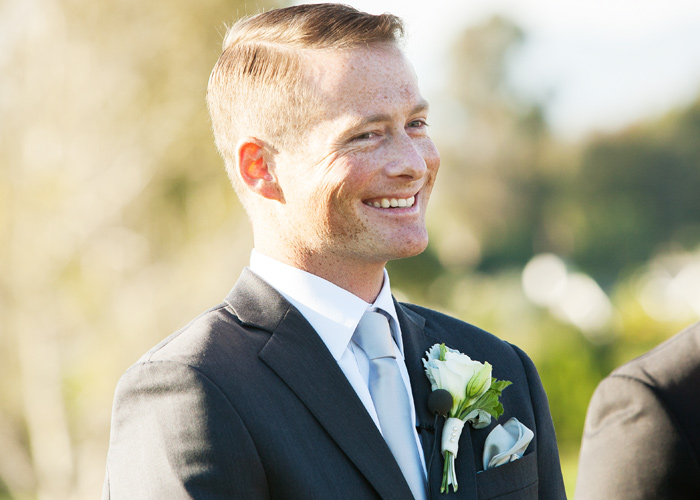 Picture of groom smiling as Bride walks down the isle.