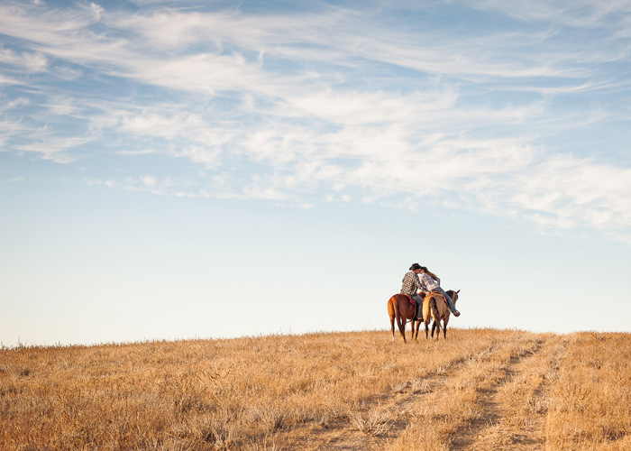 Engagement photo of couple on horses